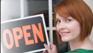 woman holding up open for business sign